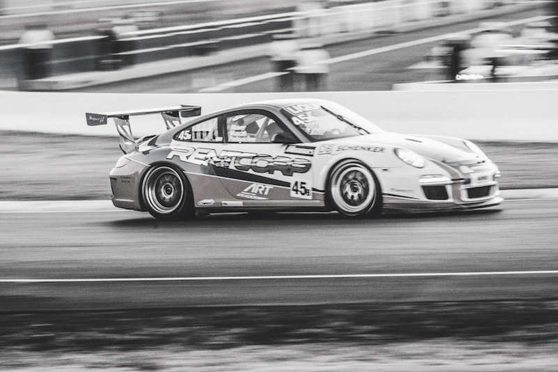 Barton Mawer racing car driver at the Bathurst 12 Hour going up Mountain Straight at Mount Panorama in a Porsche